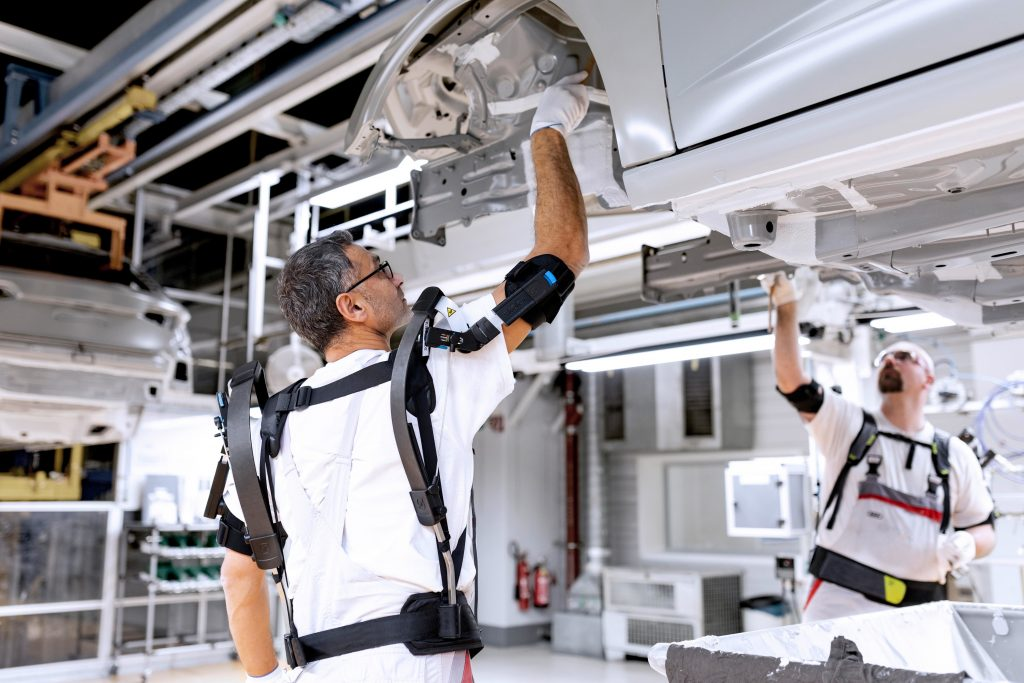 Audi is testing exoskeletons for performing overhead tasks. These external support structures help employees by protecting their joints and tiring their muscles less quickly. Employees in the paint shop are testing the exoskeletons while applying corrosio (Bild: Audi AG)